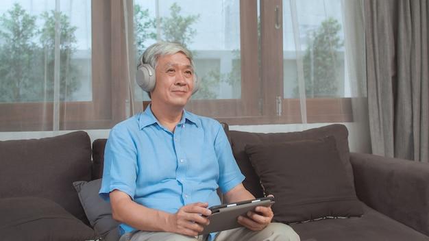 Azjatycki starszy mężczyzna relaksuje w domu. azjatycki stary męski szczęśliwy odzież hełmofon używać pastylki słuchającego podcast podczas gdy kłamający na kanapie w żywym pokoju pojęciu w domu. Darmowe Zdjęcia