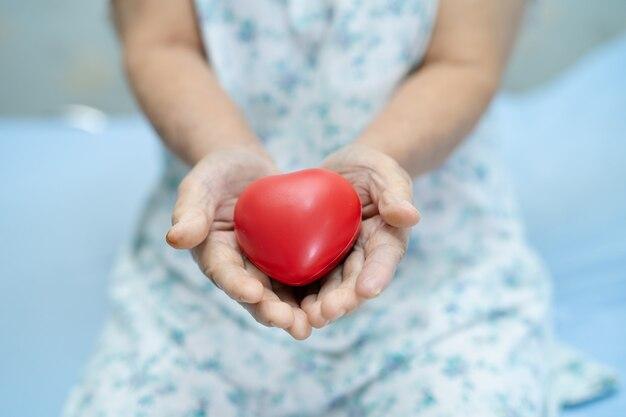 Azjatycki Starszy Pacjent Gospodarstwa Czerwone Serce. Premium Zdjęcia