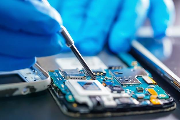 Azjatycki technik naprawiający płytę główną mikroukładu technologii elektronicznej smartfona. Premium Zdjęcia