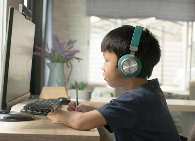 Azjatycki Uczeń Chłopiec W Słuchawkach, Zwracając Uwagę Na Naukę Online Za Pośrednictwem Komputera W Salonie W Domu, Koncepcja Nauczania W Domu. Premium Zdjęcia