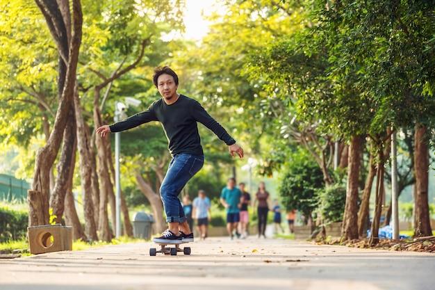 Azjatycki Wesoły Człowiek Gra Surfskate Lub Deskorolka W Parku Na świeżym Powietrzu Premium Zdjęcia