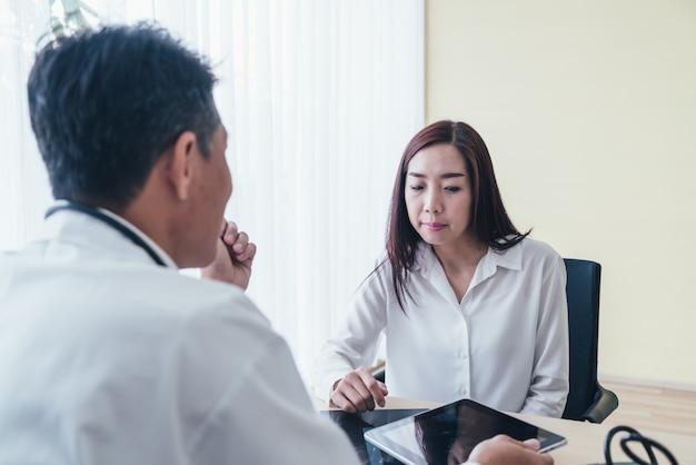 Azjatycki żeński Pacjent I Lekarka Dyskutujemy Premium Zdjęcia