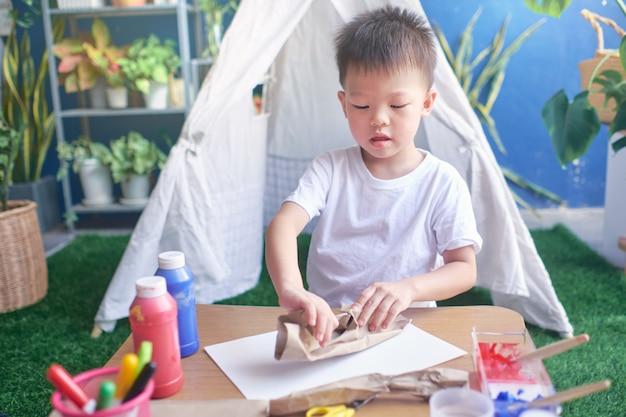 Azjatyckie 4-letnie Przedszkolak Lubi Robić Sztukę I Rękodzieło W Domu, Diy Zabawki Dla Dzieci Z Koncepcji Materiałów Nadających Się Do Recyklingu Premium Zdjęcia