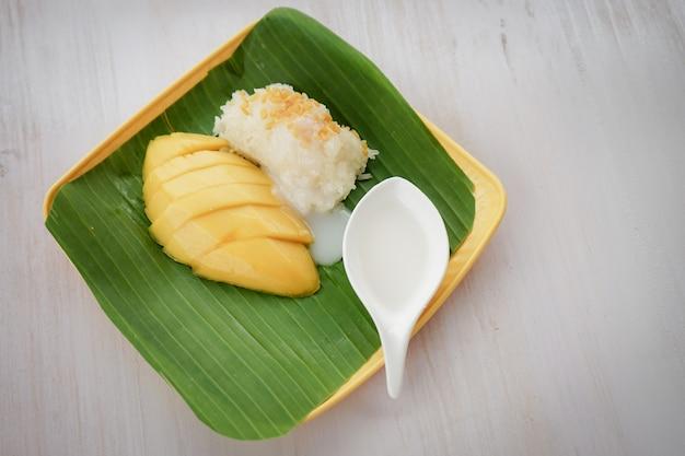 Azjatyckie jedzenie deser mango i lepki ryż umieszczone na liściach bananowca na uporządkowanym talerzu Premium Zdjęcia