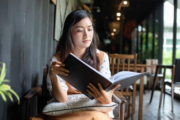 Azjatyckie kobiety czyta, uśmiechnięty i szczęśliwy relaksować w sklep z kawą po pracować w pomyślnym biurze. Premium Zdjęcia
