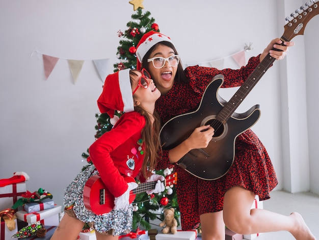 Azjatyckie kobiety i dzieci obchodzą boże narodzenie, grając w domu na gitarze Premium Zdjęcia