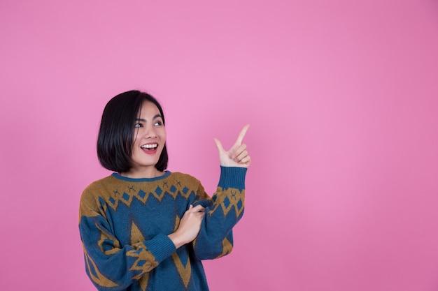 Azjatyckie kobiety i przestrzeń życiowa, która jest wskazana na różowym tle palca. Premium Zdjęcia