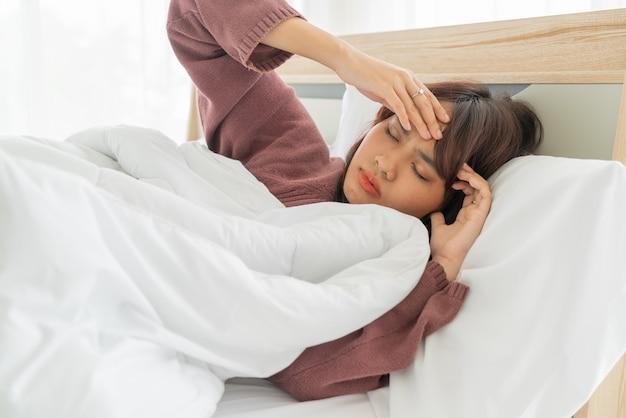 Azjatyckie Kobiety Migrena I Dosypianie Na łóżku Premium Zdjęcia