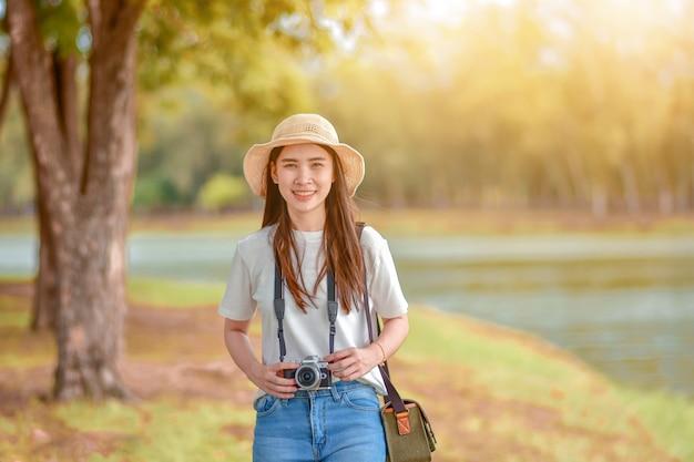 Azjatyckie kobiety podróżują w naturze z kamerą bierze fotografię Premium Zdjęcia