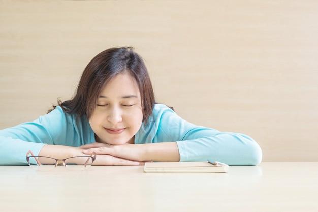 Azjatyckie kobiety spać przez kłamał na biurku z szczęśliwą twarz w czasie odpoczynku od czytania książki Premium Zdjęcia