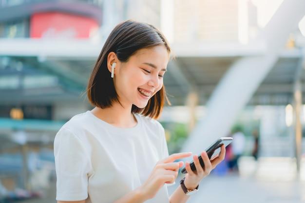 Azjatyckie kobiety szczęśliwe uśmiechnięte słuchają muzyki z białych słuchawek. Premium Zdjęcia