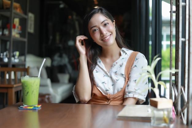 Azjatyckie kobiety uśmiechnięte i szczęśliwe relaksować z zieloną herbatą w sklep z kawą Premium Zdjęcia