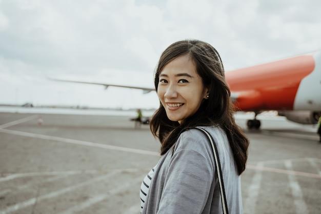 Azjatyckie Kobiety W Ciąży Ciągnie Walizki Podczas Gdy Chodzący Na Pasie Startowym Premium Zdjęcia