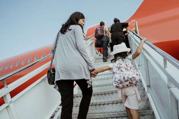 Azjatyckie Kobiety W Ciąży I Ich Córki Wchodzą Po Schodach Do Samolotu Premium Zdjęcia