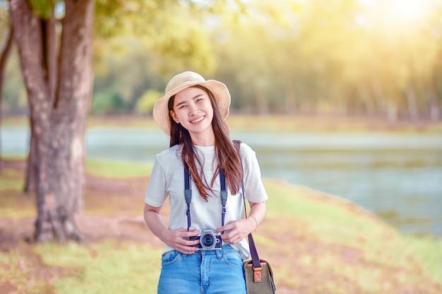 Azjatyckie kobiety w parku z aparatem fotograficznym Premium Zdjęcia