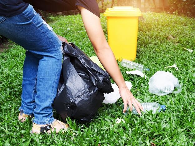 Azjatyckie kobiety zbierają śmieci w czarnych workach z żółtymi śmieciami umieszczonymi w ogrodzie. Premium Zdjęcia