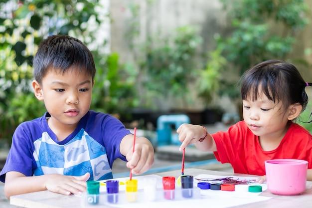 Azjatyckie Rodzeństwo Rysuje I Maluje Kolory Na Papierze W Pokoju. Premium Zdjęcia
