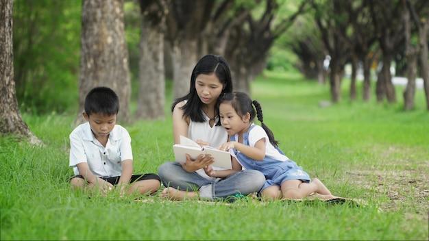 Azjatyckie Rodziny Wspólnie Robią Zajęcia, Czytając Książki W Parku Premium Zdjęcia