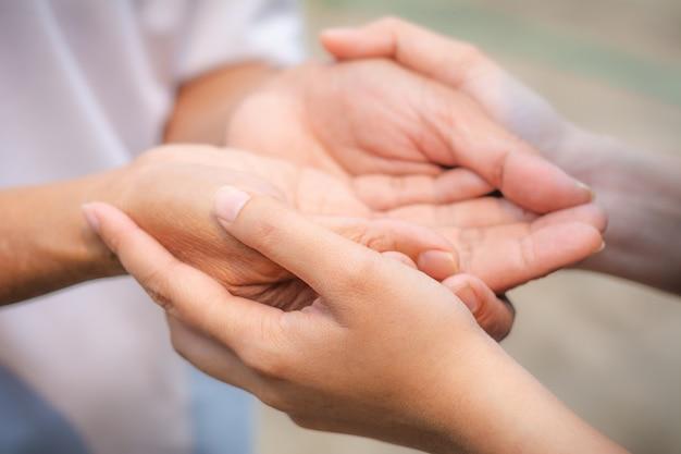 Azjatyckie Starszy I Azjatyckie Młode Trzymając Się Za Ręce. Premium Zdjęcia