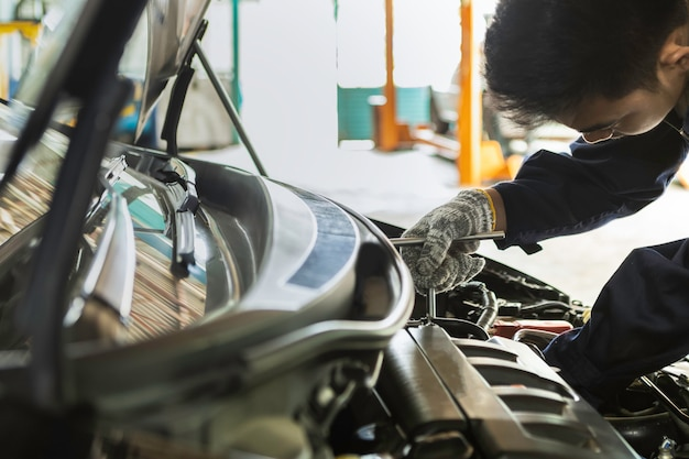 Azjatyckiego mężczyzna auto mechanik używa wyrwanie obsługiwać samochód w garażu. Premium Zdjęcia