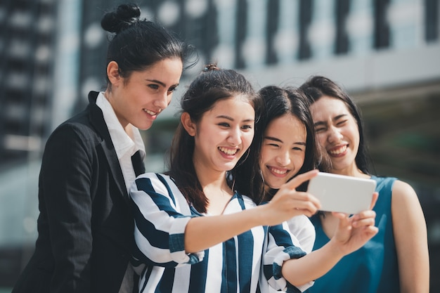 Azjatyckiego stylu życia bizneswoman najlepsi przyjaciele ono uśmiecha się i ma zabawy chodzącego selfie przy miastem Premium Zdjęcia