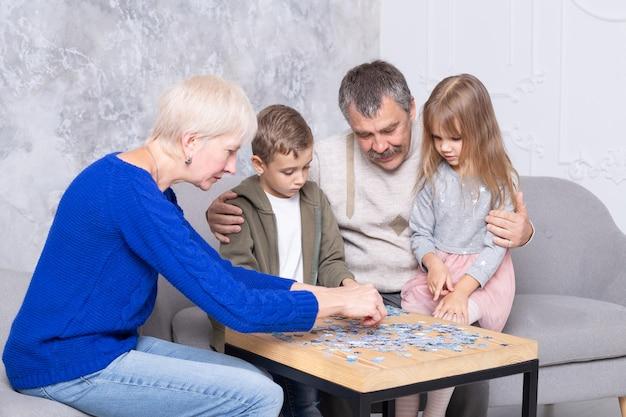 Babcia, Dziadek I Wnuczka Zbierają Puzzle Przy Stole W Salonie. Szczęśliwa Rodzina Spędza Czas Razem, Grając W Gry Edukacyjne Premium Zdjęcia