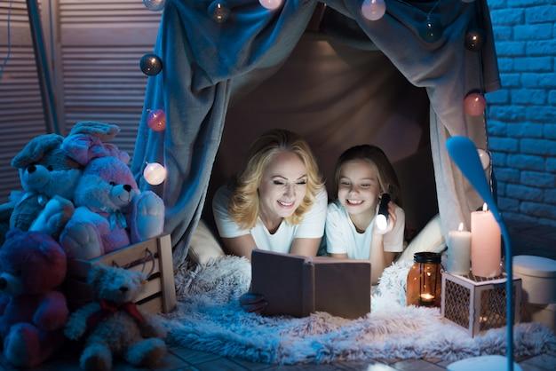 Babcia I Wnuczka Czytają Książkę W Kocu Domu W Nocy W Domu. Premium Zdjęcia
