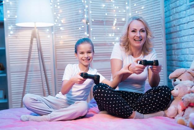 Babcia I Wnuczka Grają W Gry Wideo W Nocy W Domu. Premium Zdjęcia