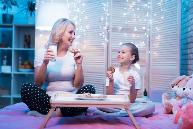 Babcia I Wnuczka Jedzą W Domu Ciasteczka Z Mlekiem. Premium Zdjęcia