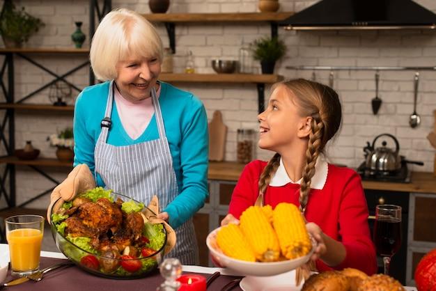 Babcia i wnuczka patrzą na siebie i trzymają jedzenie Darmowe Zdjęcia