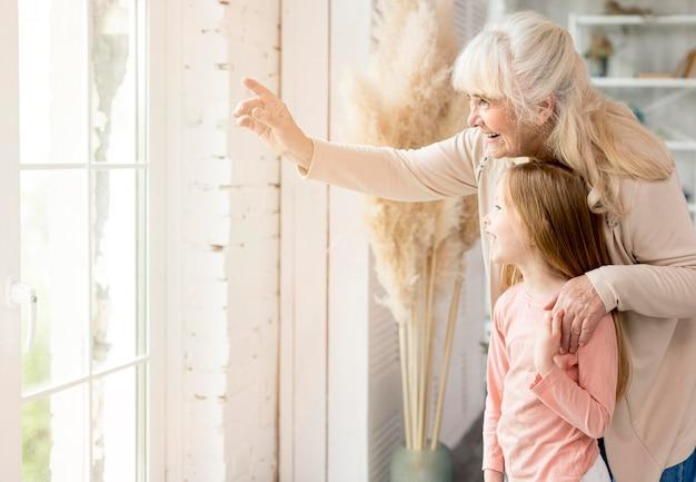 Babcia Z Dziewczyną Patrzeje Na Okno W Domu Darmowe Zdjęcia