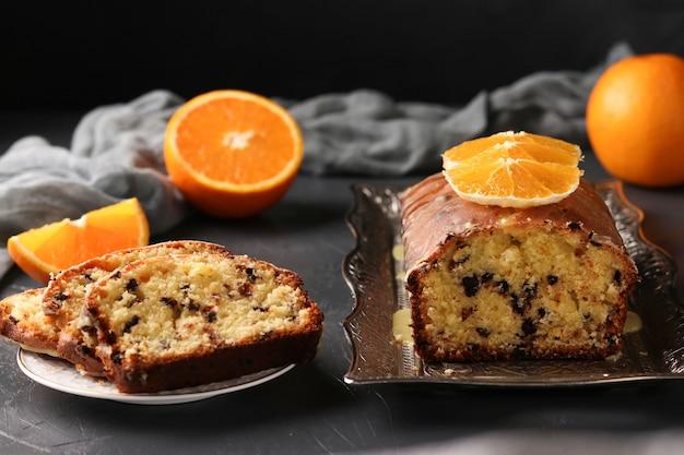 Babeczka Z Pomarańczami I Czekoladą Znajduje Się Na Tacy Na Ciemnym Tle Premium Zdjęcia
