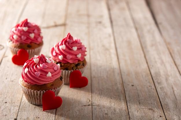 Babeczki Ozdobione Serduszkami Z Cukru Na Walentynki Na Drewnianym Stole Premium Zdjęcia