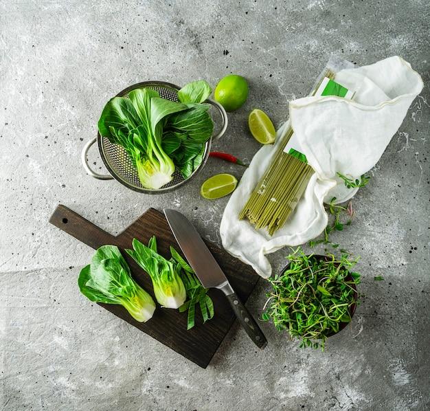 Baby Bok Choi Połówki, Niegotowane Zielonej Herbaty Makaron, Limonki, Zielone Kiełki Na Szarym Tle. Widok Z Góry, Kwadratowy Obraz Premium Zdjęcia