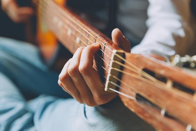 Bądź W Domu Bądź Bezpieczny. Młoda Kobieta Siedzi W Domu I Gra Na Gitarze, Ręce Z Bliska. Teen Dziewczyna Uczy Się Grać Piosenki I Pisać Muzykę. Hobby Styl życia Relaks Koncepcja Edukacji Wypoczynek Instrument. Premium Zdjęcia