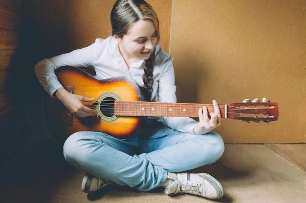 Bądź W Domu Bądź Bezpieczny. Młoda Kobieta Siedzi W Pokoju Na Podłodze I Gra Na Gitarze W Domu. Teen Dziewczyna Uczy Się Grać Piosenki I Pisać Muzykę. Hobby Styl życia Relaks Koncepcja Edukacji Wypoczynek Instrument. Premium Zdjęcia