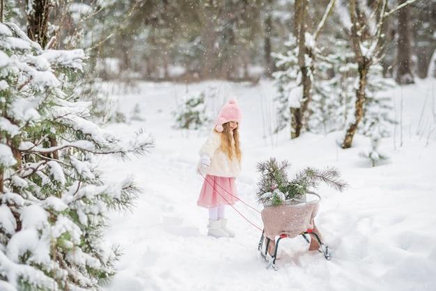 Bajka Piękna Dziewczyna W Białym Futrze Toczy Sanki W Zimowym, Ośnieżonym Lesie Z Choinkami Premium Zdjęcia