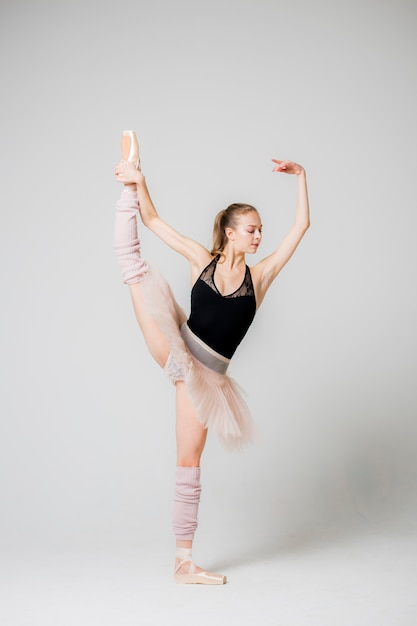 Balerina utrzymuje równowagę stojąc na jednej nodze. Premium Zdjęcia
