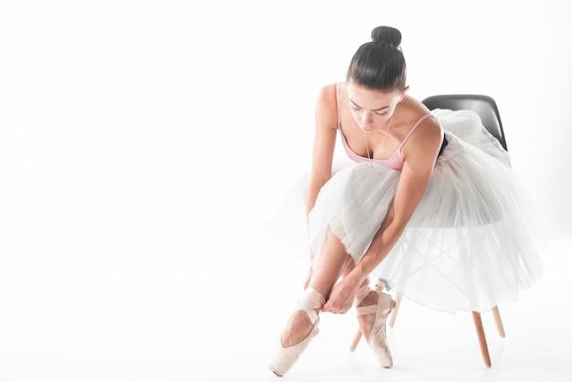 Baletniczego tancerza obsiadanie na krześle wiąże up jej pointe buty przeciw białemu tłu Darmowe Zdjęcia
