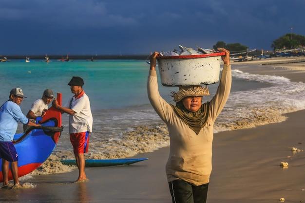 Bali indonezja, sierpień, - 6, 2017: balijski fishmonger niesie ryba w basenie przy ranku rynkiem w kedonganan - przechodzień ikan, jimbaran plaża Premium Zdjęcia
