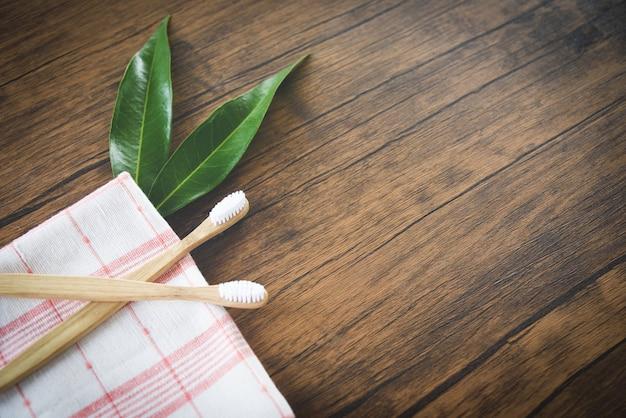 Bambusowa szczoteczka do zębów i zielony liść na rustykalnym drewnie Premium Zdjęcia