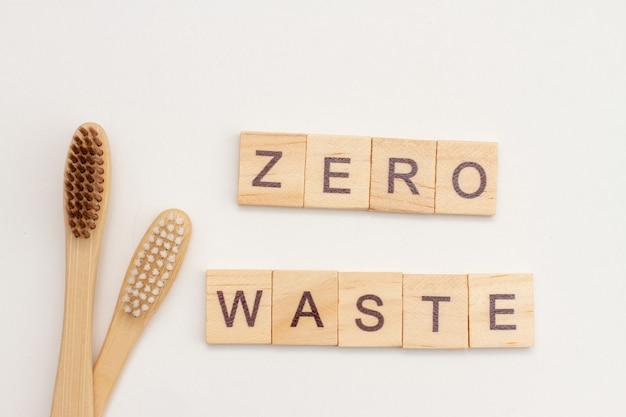Bambusowe Szczoteczki Do Zębów I Napis Zero Waste Wykonane Z Drewnianych Kostek Na Białym Tle. Koncepcja Przyjazna Dla środowiska Premium Zdjęcia
