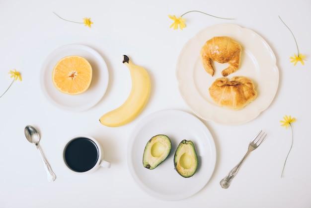 Banan; rogaliki; połówki awokado; filiżanka kawy na białym tle z łyżką i widelcem na białym tle Darmowe Zdjęcia