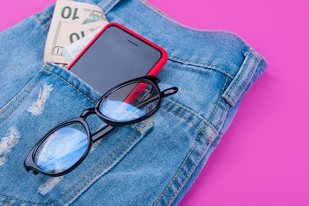 Baner Na Różowej Powierzchni Z Niebieskimi Dżinsami, Pieniędzmi, Słuchawkami, Telefonem, Okularami. Premium Zdjęcia