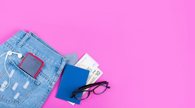 Baner Na Różowym Tle Z Niebieskimi Dżinsami, Pieniądze, Słuchawki, Telefon Internetowy 5g, Okulary. Premium Zdjęcia