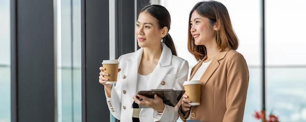 Baner, Strona Internetowa Lub Szablon Okładki Dwóch Azjatyckich Przedsiębiorców Rozmawiać Podczas Przerwy Na Kawę W Nowoczesnym Biurze Premium Zdjęcia
