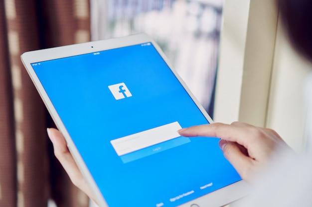 Bangkok, Tajlandia - 11 Czerwca 2018: Ręka Naciska Przycisk Facebook Na Apple Ipad Pro Premium Zdjęcia