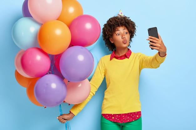 Bardzo Młoda Kobieta Trzyma Wielobarwne Balony, Pozując W żółtym Swetrze Darmowe Zdjęcia