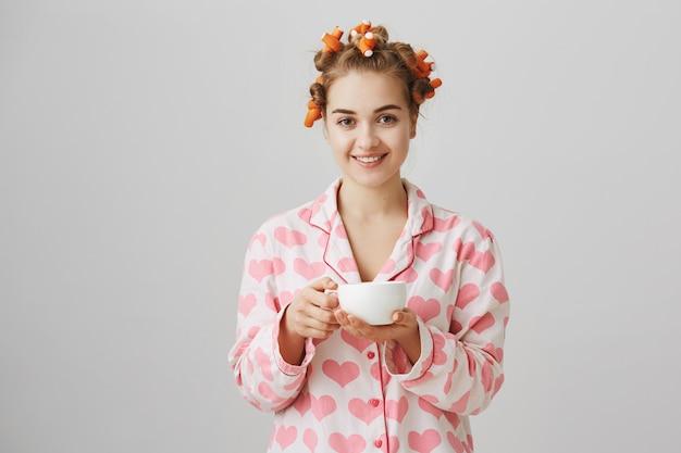 Bardzo Młoda Kobieta W Lokówki I Piżamie Picia Porannej Kawy Darmowe Zdjęcia