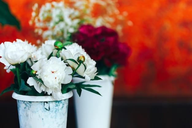 Bardzo piękne piony w wazonach stojących na stole, prezent dla kobiety Premium Zdjęcia